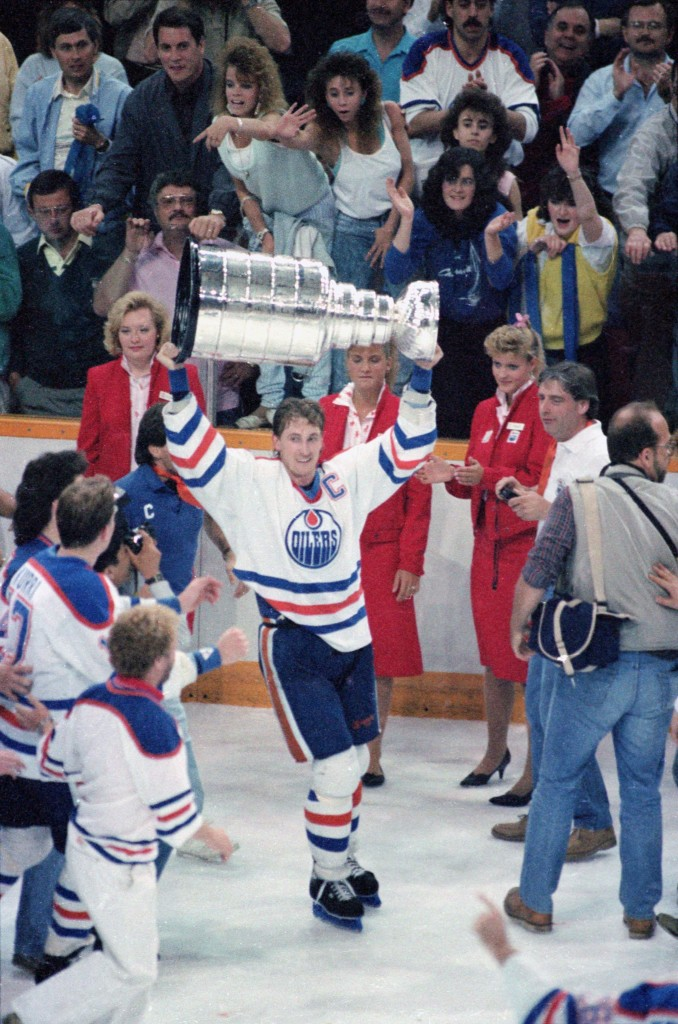 Wayne Gretzky hoists the 1987 Stanley Cup as Susan Darrington and a few other usherette's look on. Photo by Getty Images.