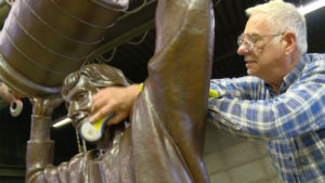 Don Begg polishes the Gretzky Statue